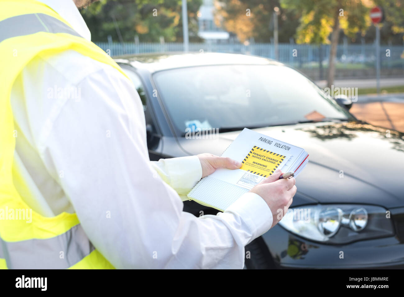 Police officer giving a ticket fine for parking violation - Stock Image