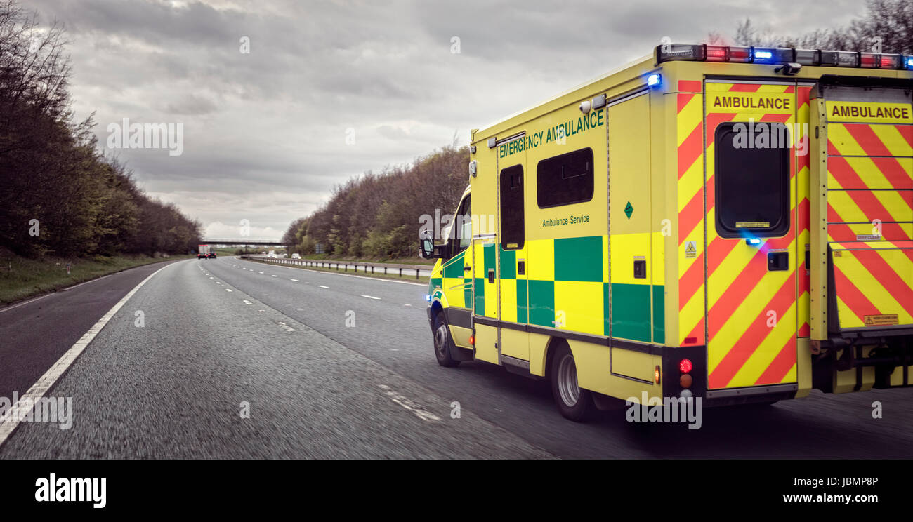 British ambulance responding to an emergency in hazardous bad weather driving conditions on a UK motorway Stock Photo