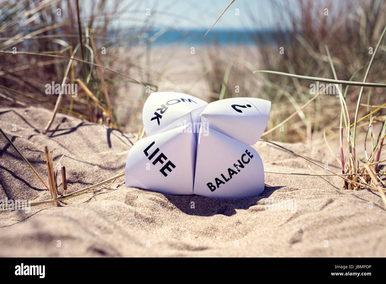 Origami fortune teller on vacation at the beach concept for work life balance choices - Stock Image