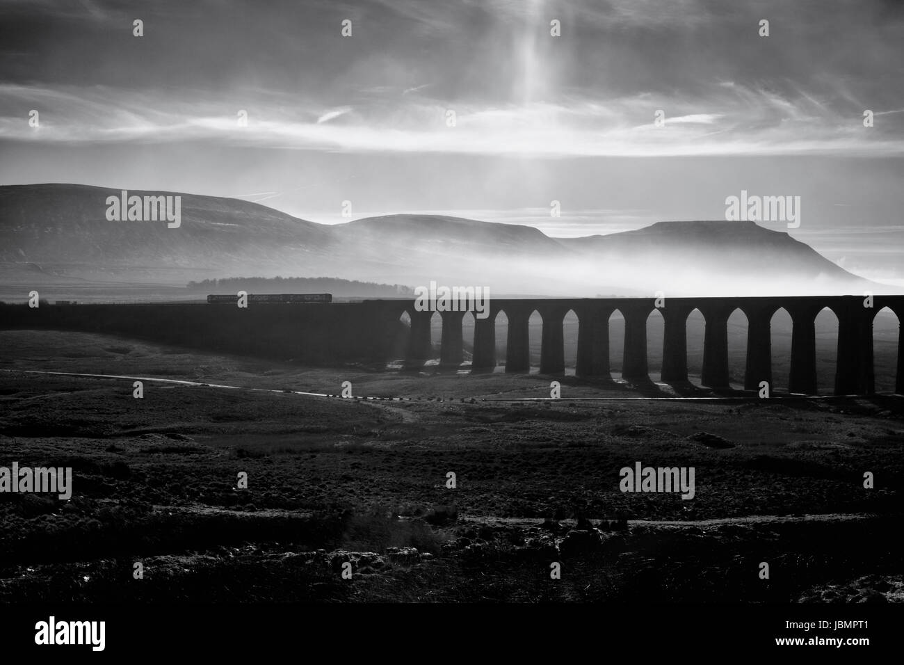 Northern Rail 1151 Carlisle - Leeds train  passes Ribblehead viaduct with Ingleborough behind - Stock Image