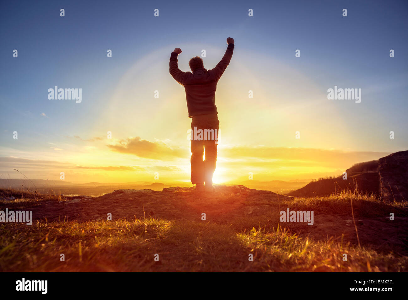 Happy man celebrating winning success or worship and praise against sunset - Stock Image