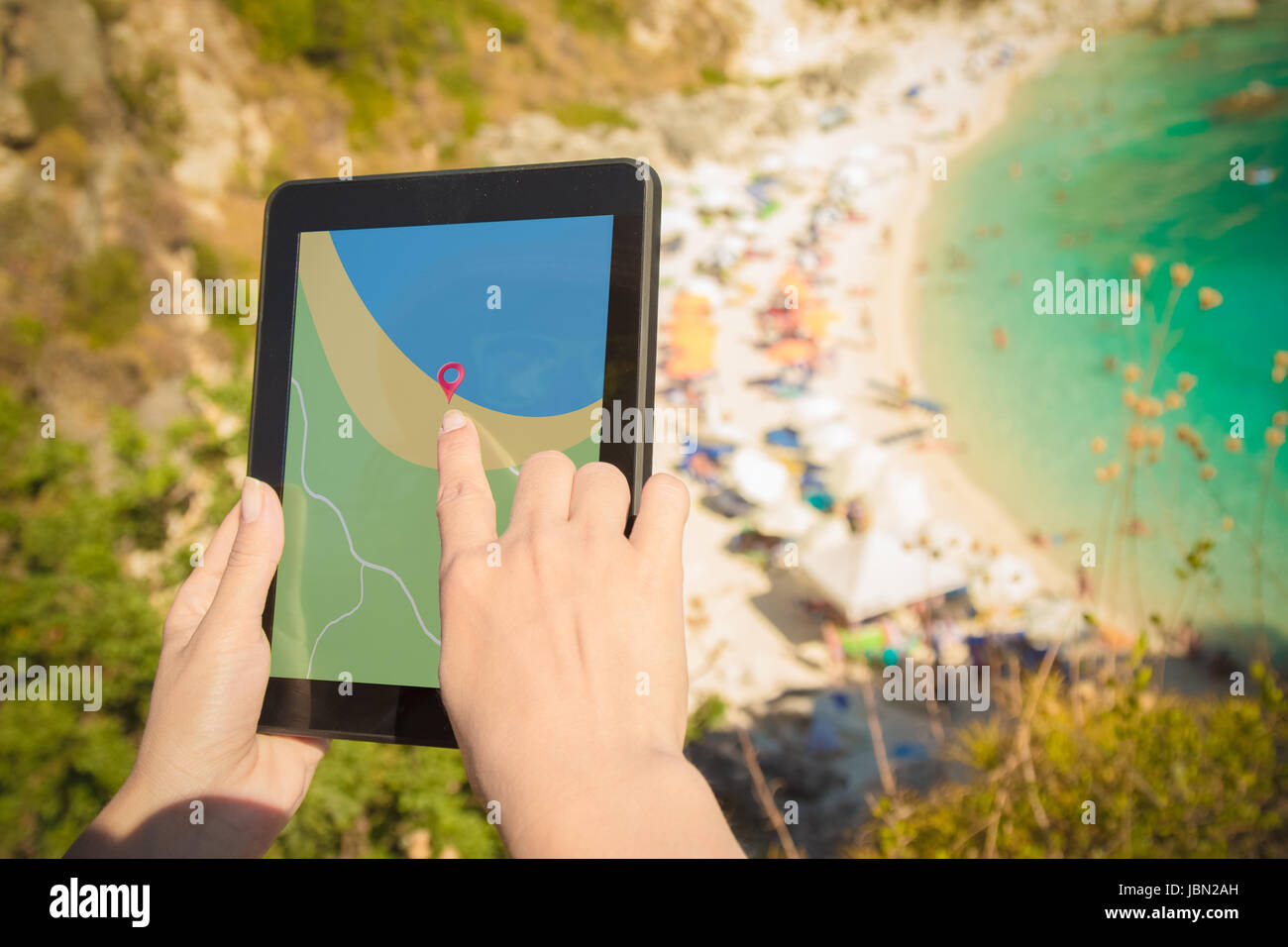 Female hands holding digital tablet device with gps navigation map application on the hill above the beautiful beach. - Stock Image