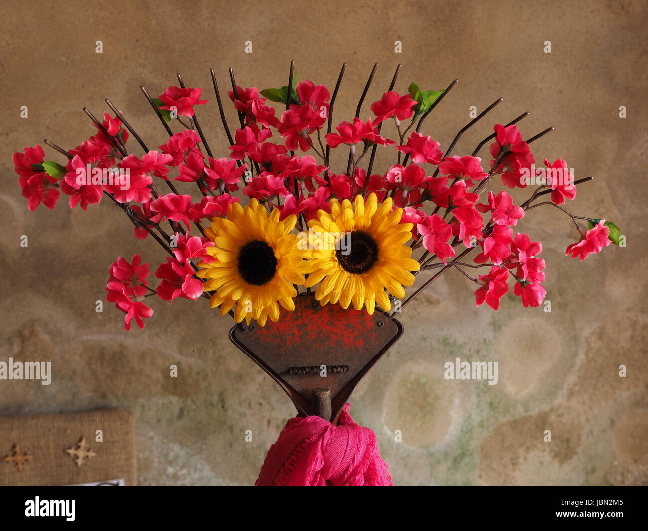 garden rake decorated with artificial red and yellow flowers to resemble a face in Orton church Cumbria, England - Stock Image