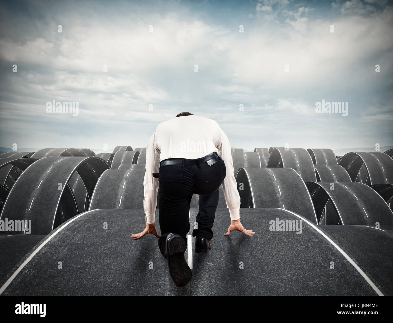 Businessman ready to start on complicated roads - Stock Image
