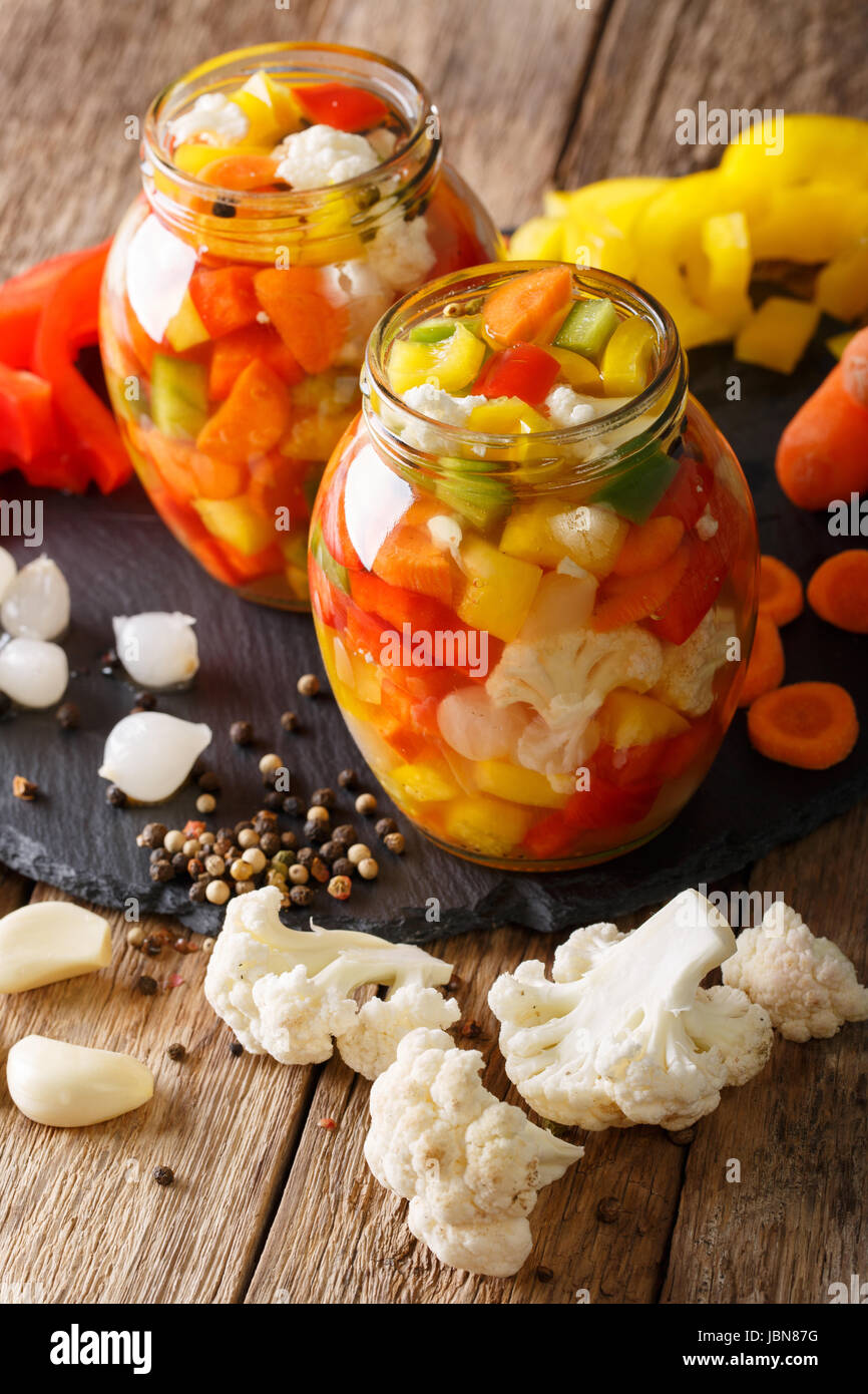 Spicy Homemade Pickled Giardiniera with Peppers, Carrots and Cauliflower close-up in glass jars. Vertical Stock Photo