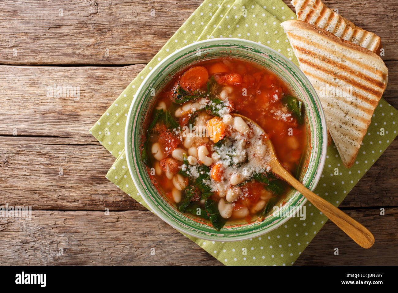 Tomato soup with beans, spinach and parmesan close-up on the table. horizontal view from above - Stock Image