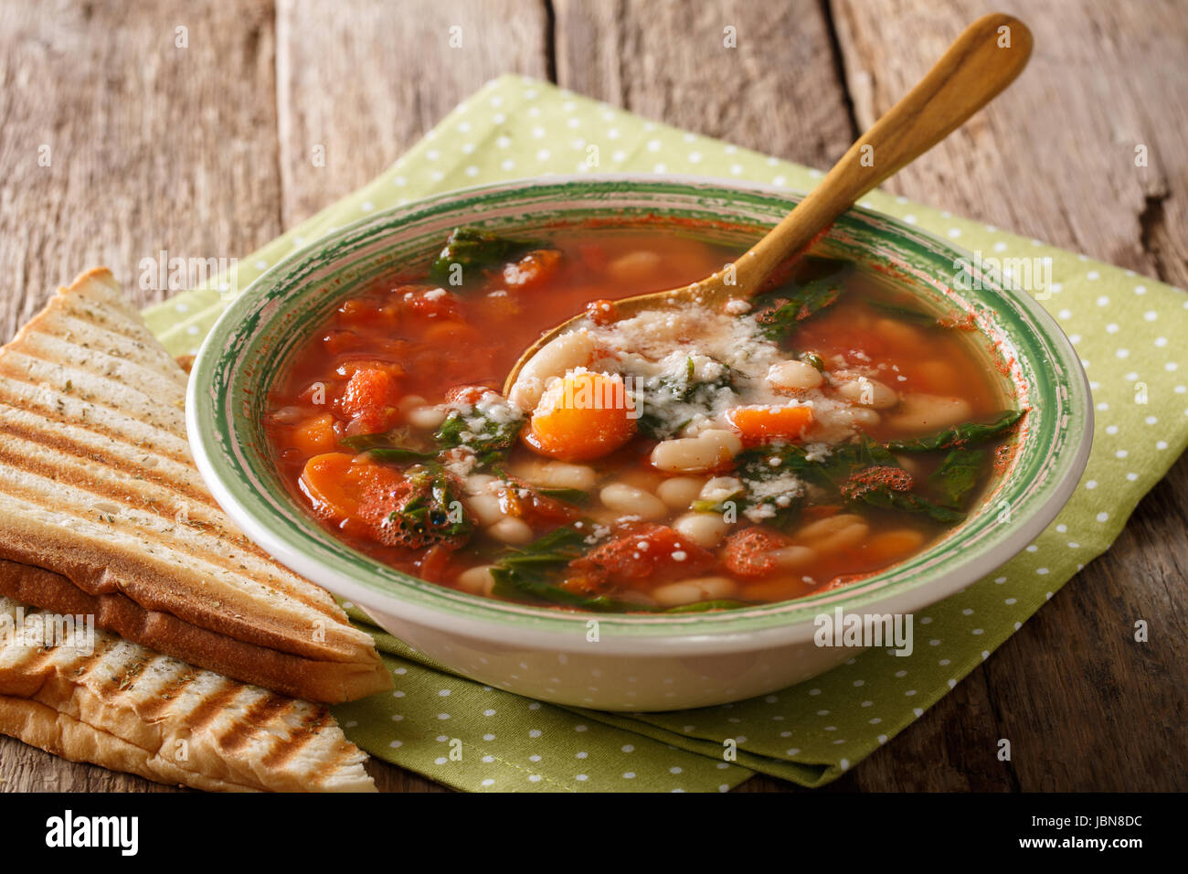 Tomato soup with beans, spinach and parmesan close-up on the table. Horizontal - Stock Image