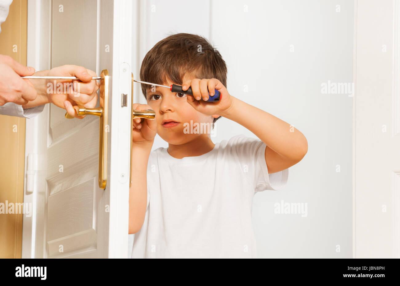 Portrait Of Kid Boy Drawing Up Bolt Of Door Handle Using Screwdriver Stock Photo Alamy