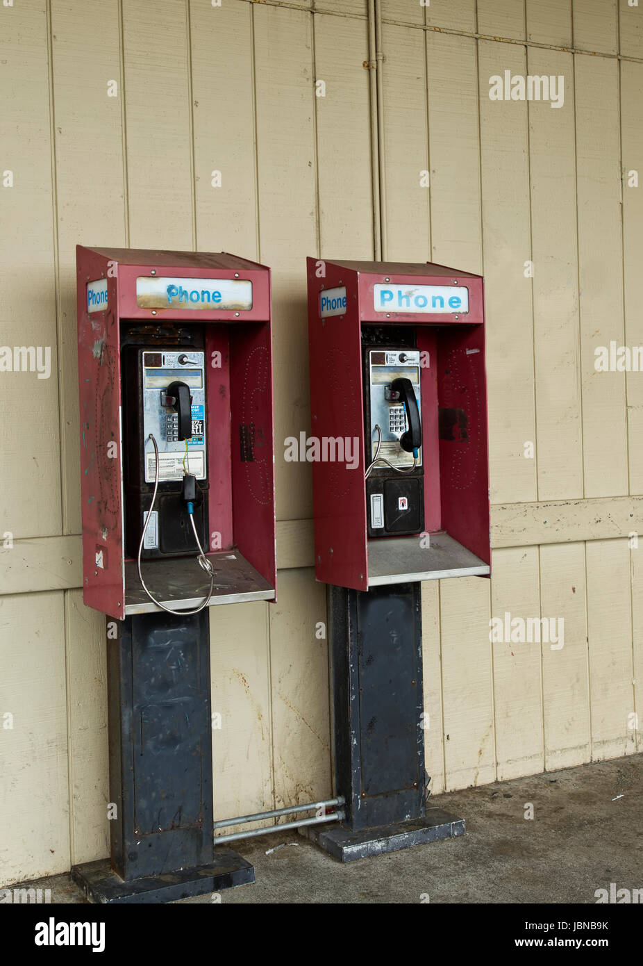 Abandoned public pay telephones with coin release slot. - Stock Image