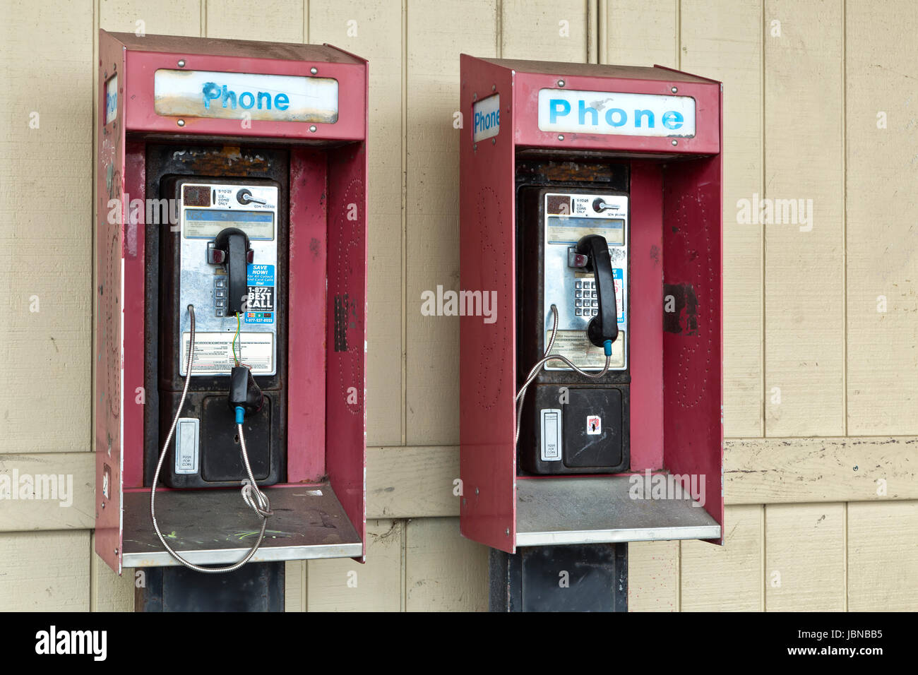 Abandoned coin operated public pay telephone with coin release slot. - Stock Image