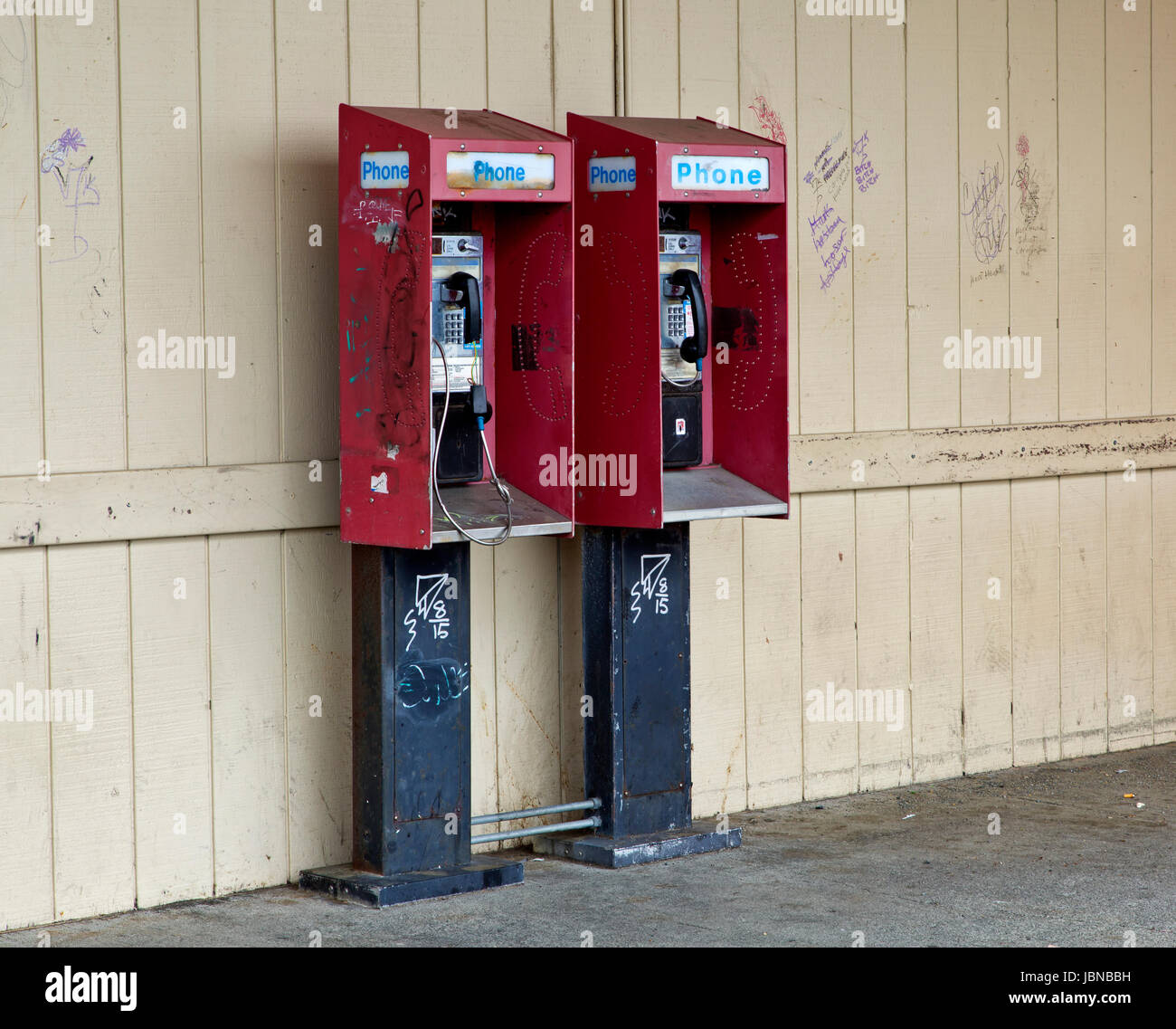 Abandoned coin operated public pay telephones with coin release slot,  graffiti on wall & telephones. . - Stock Image
