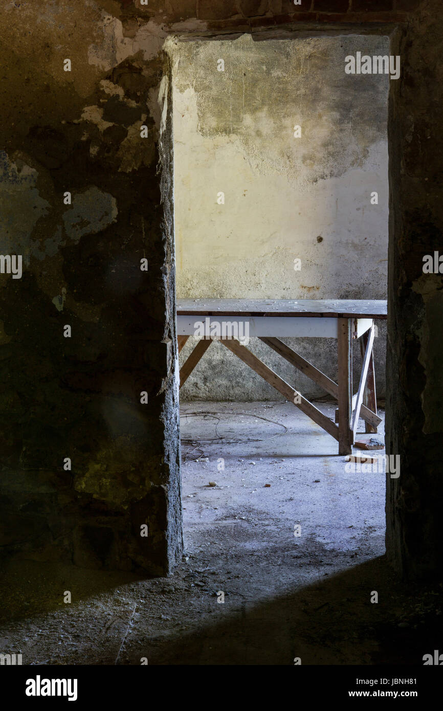 The Table- An old farm table is seen through a doorway in an abandoned home in Tuscany, Italy - Stock Image