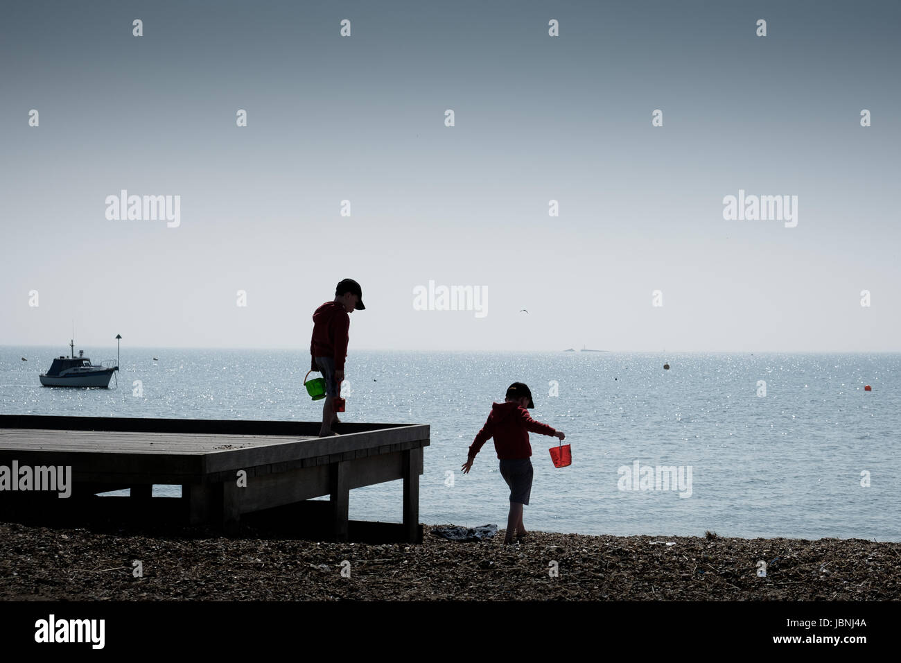 twin children bucket and spades at the beach silhouette Stock Photo
