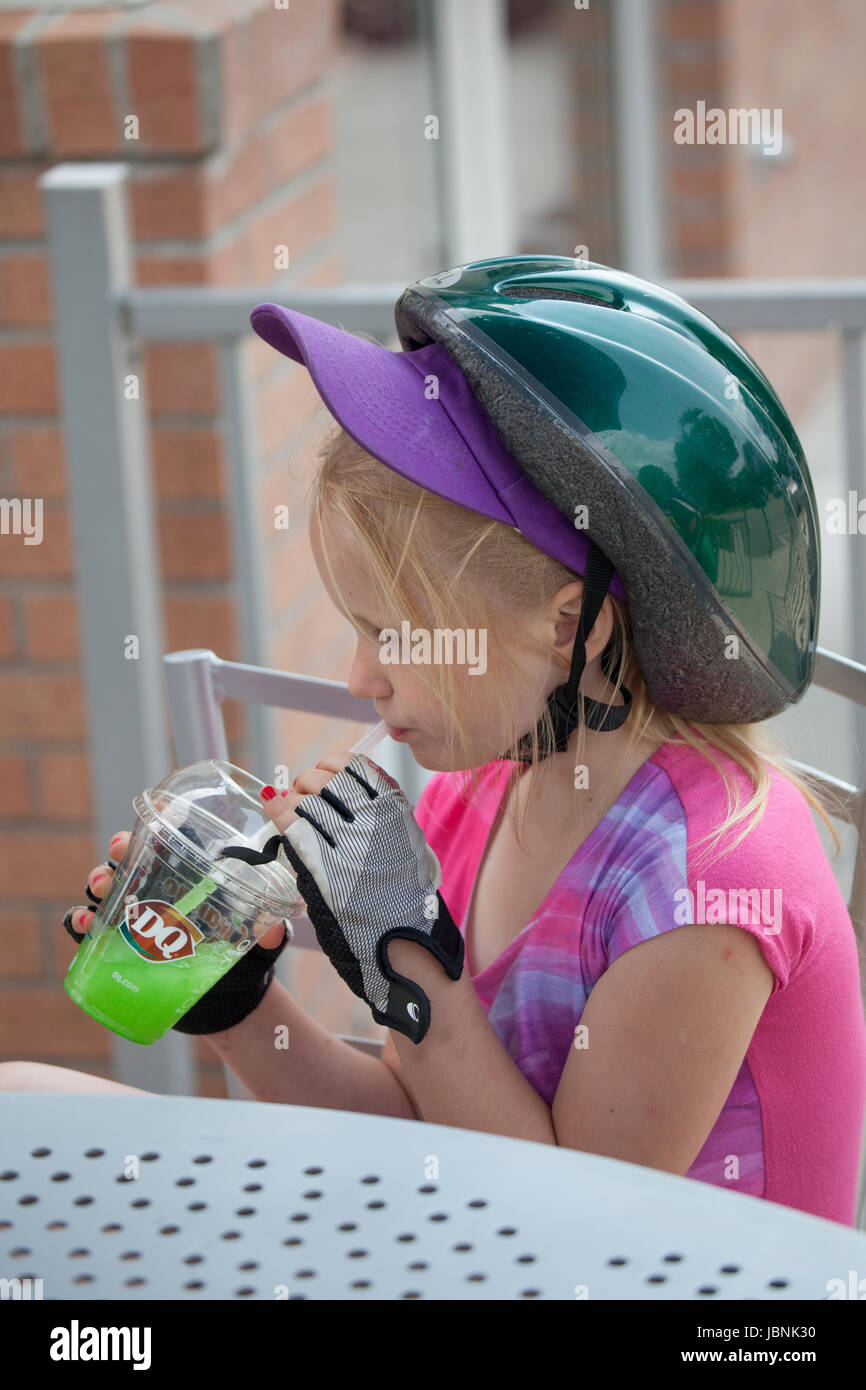 Girl with bicycle helmet taking a break to hydrate with juice. Minneapolis Minnesota MN USA - Stock Image