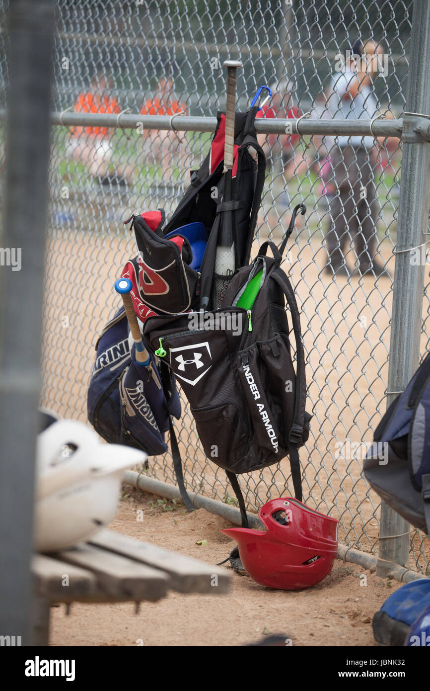 Baseball equipment hanging on the fence in dugout during game. St Paul Minnesota MN USA - Stock Image