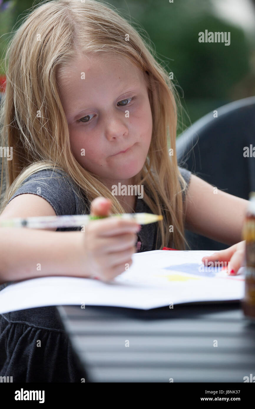 Girl age 7 concentrating on her drawing. St Paul Minnesota MN USA - Stock Image