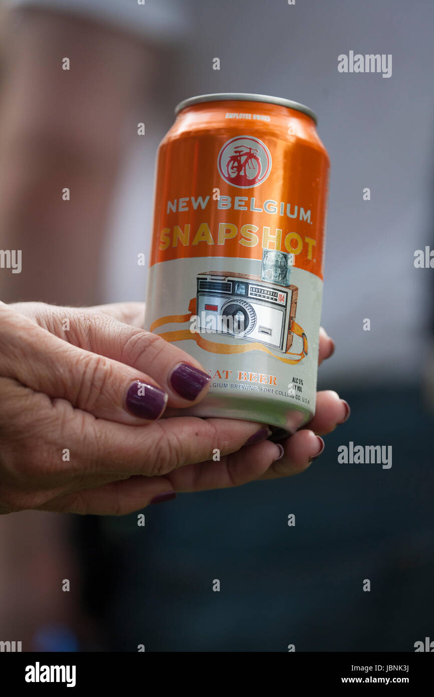 Woman holding an interesting can of Snapshot New Belgium Beer featuring an Instamatic Camera. Clitherall Minnesota - Stock Image