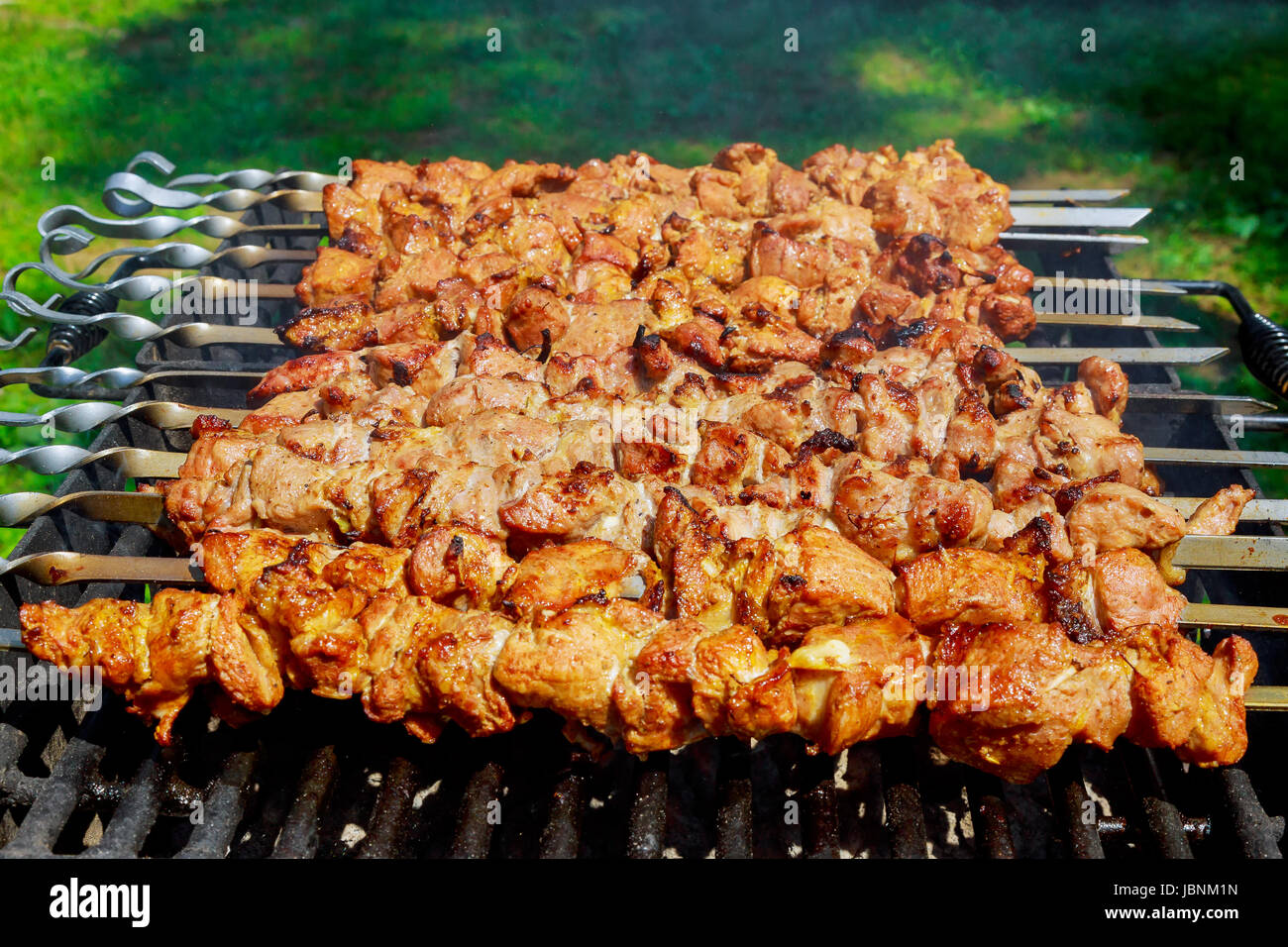 Pork on skewers cooked on barbecue grill. - Stock Image