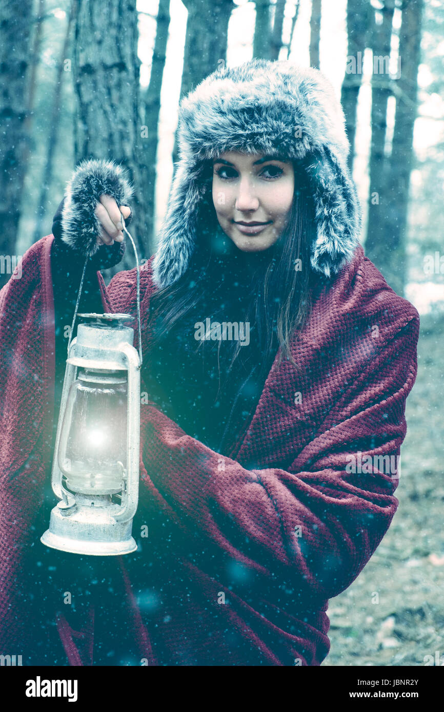 Woman with lantern in winter forest - Stock Image