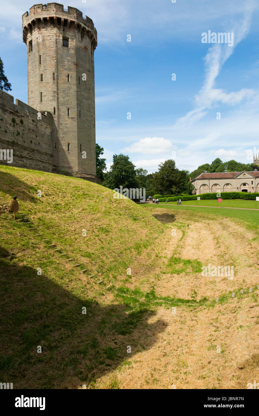 Guy's tower and rising above the ramparts and moat / grass covered dry moat of Warwick castle in Warwickshire, - Stock Image