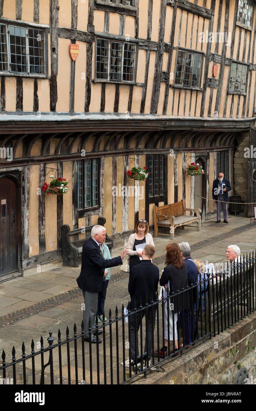 Brethren / Brother (a retired Ex-Serviceman) resident leads / guides a tour group of tourists around The Lord Leycester - Stock Image