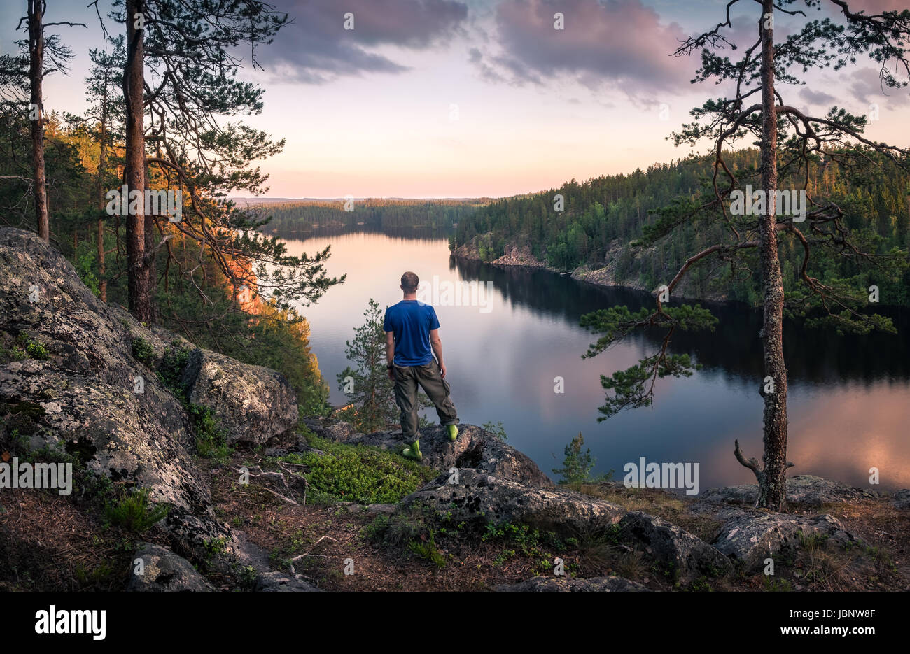 Hiker standing top of the hill front of beautiful idyllic landscape - Stock Image