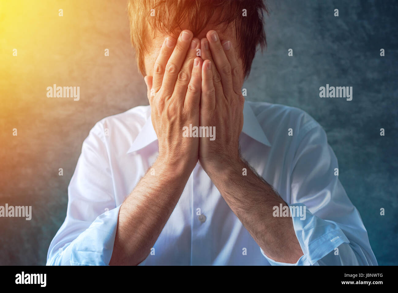Hopeless depressive businessman in white shirt with roll up sleeves, hands covering face, crying in despair - Stock Image