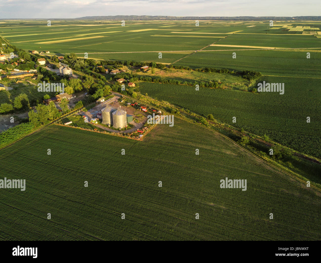 Aerial view of countryside landscape from drone pov - cultivated fields, silos and village in the distance - Stock Image