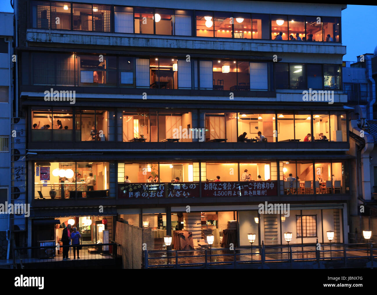 Diners eat in a multi-layered restaurant on the banks of The Kamo River (Kamo-gawa), Kyoto, Japan - Stock Image