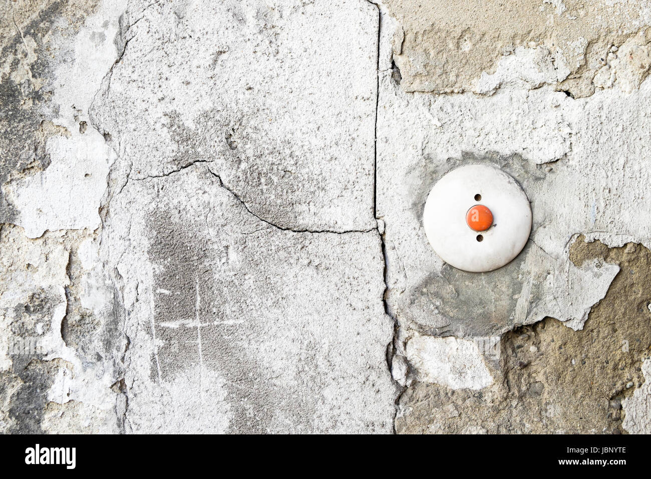 A retro red doorbell buzzer, surrounded by cracked concrete and flaking stucco in Vienna, Austria. - Stock Image