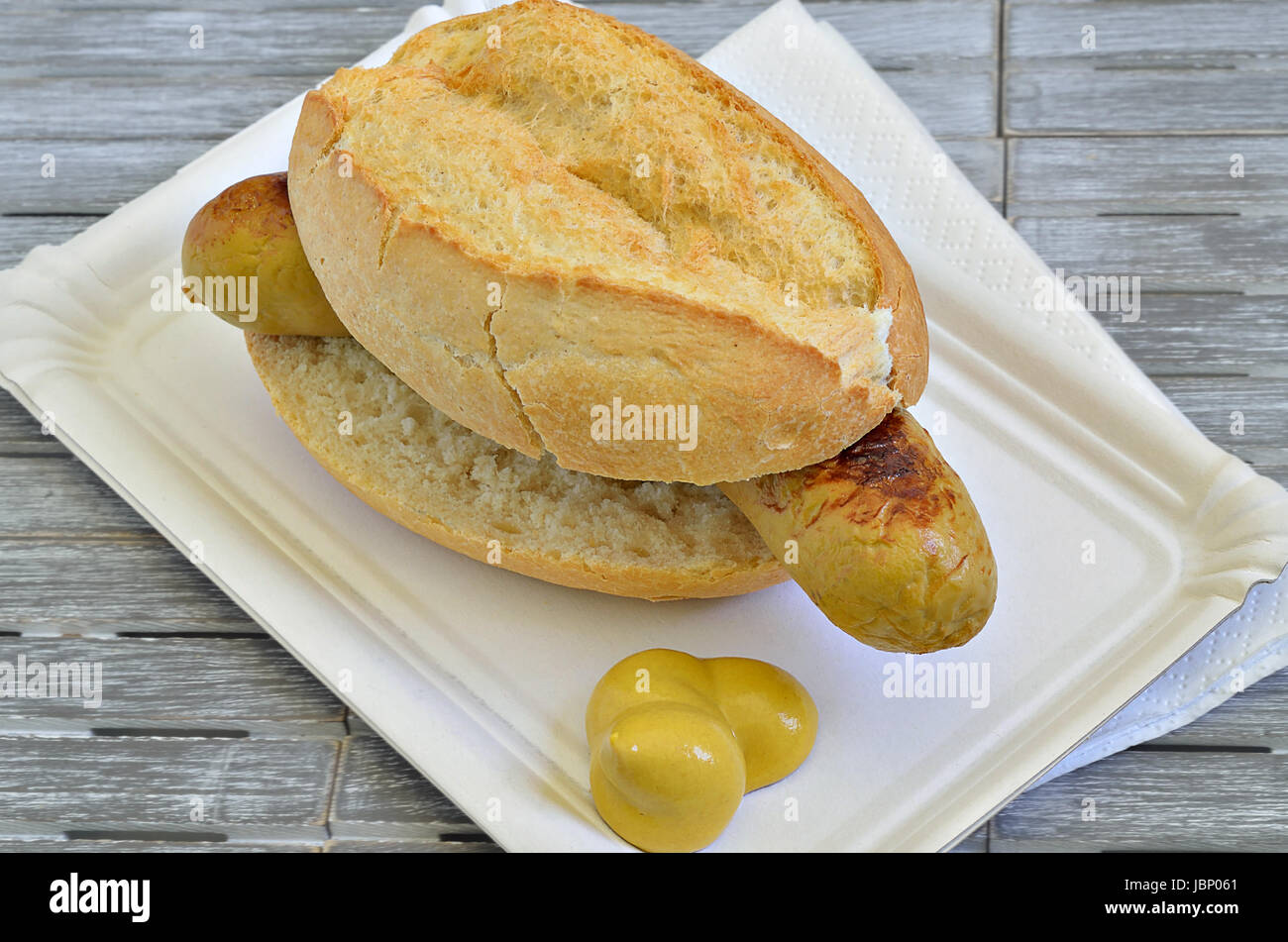 grilled sausage in roll on white paper plate with mustard, close up, macro, full frame, gray background Stock Photo