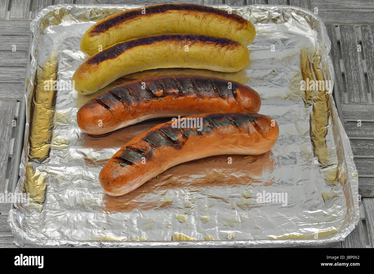 grilled sausages on grill with silver foil, close up, macro, full frame Stock Photo