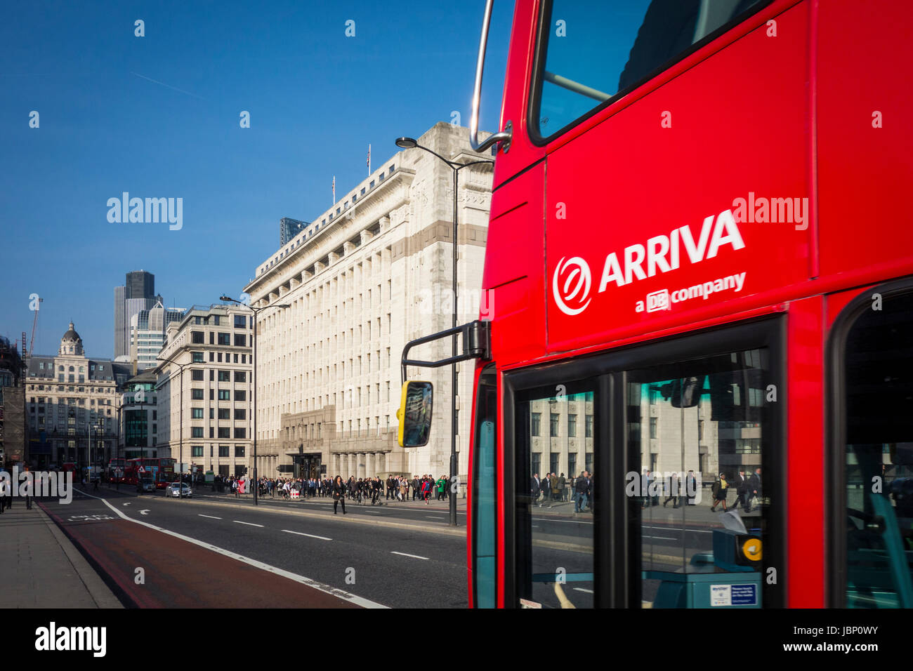 Arriva red London bus travelling over London Bridge, UK - Stock Image