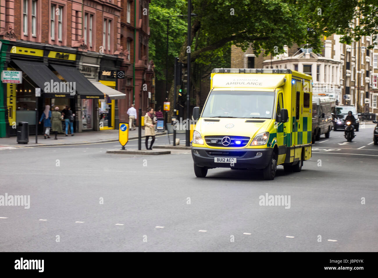 UK Ambulance driving at speed over an empty junction in London - Stock Image