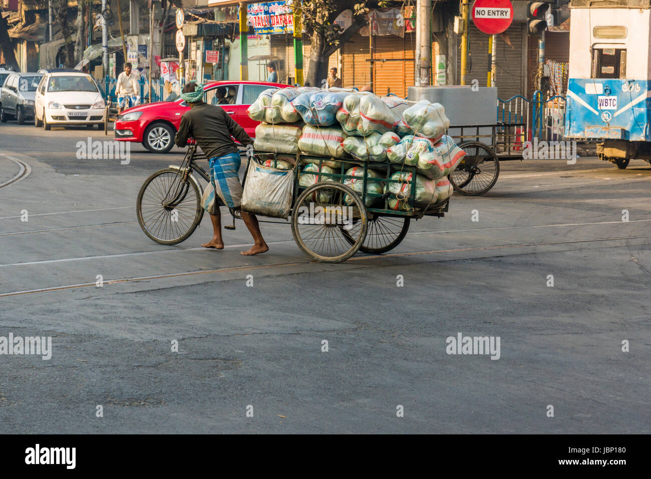 A heavily loaded cycle rikshaw is crossing a road in the suburb Esplanade Stock Photo