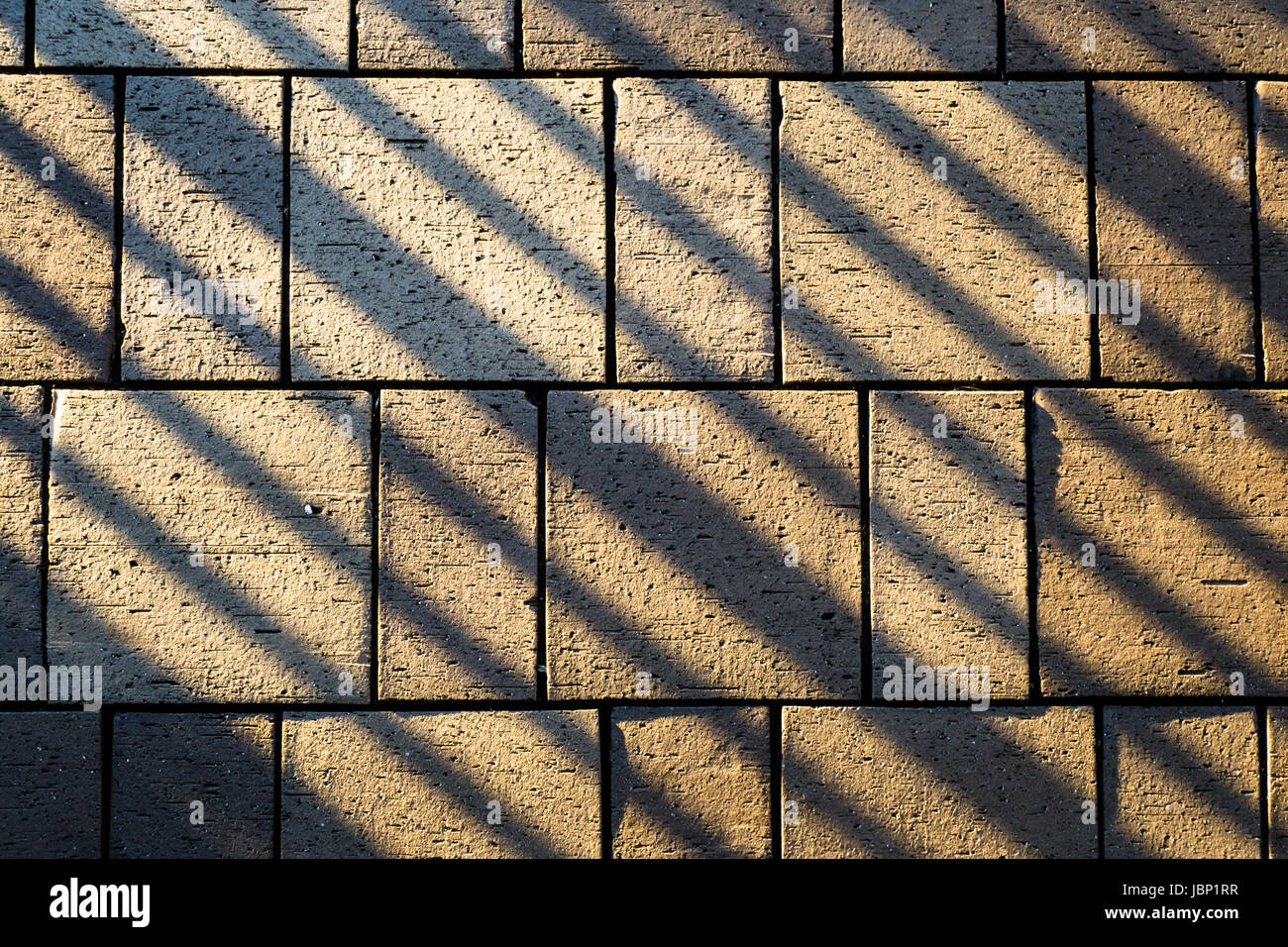 Paving stones of concrete laid on ground illuminated by sun and with railing shadow lines at an angle - Stock Image