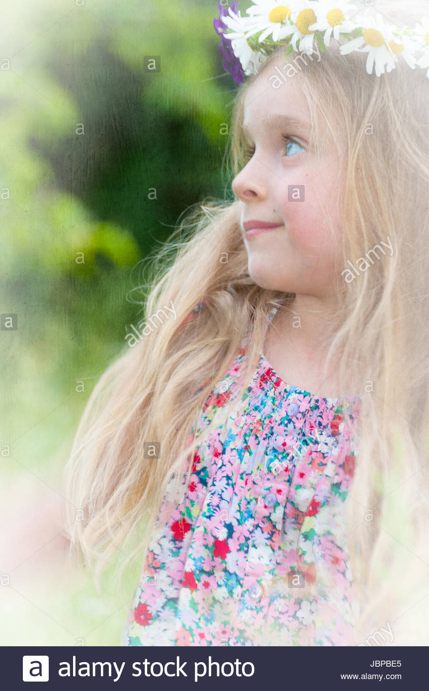 cute little girl with a wreath of flowers in her blonde hair stock