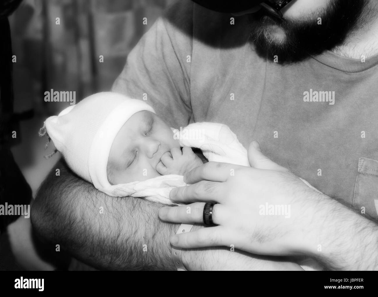 New Father Holds His Infant Daughter While She sleeps - Stock Image