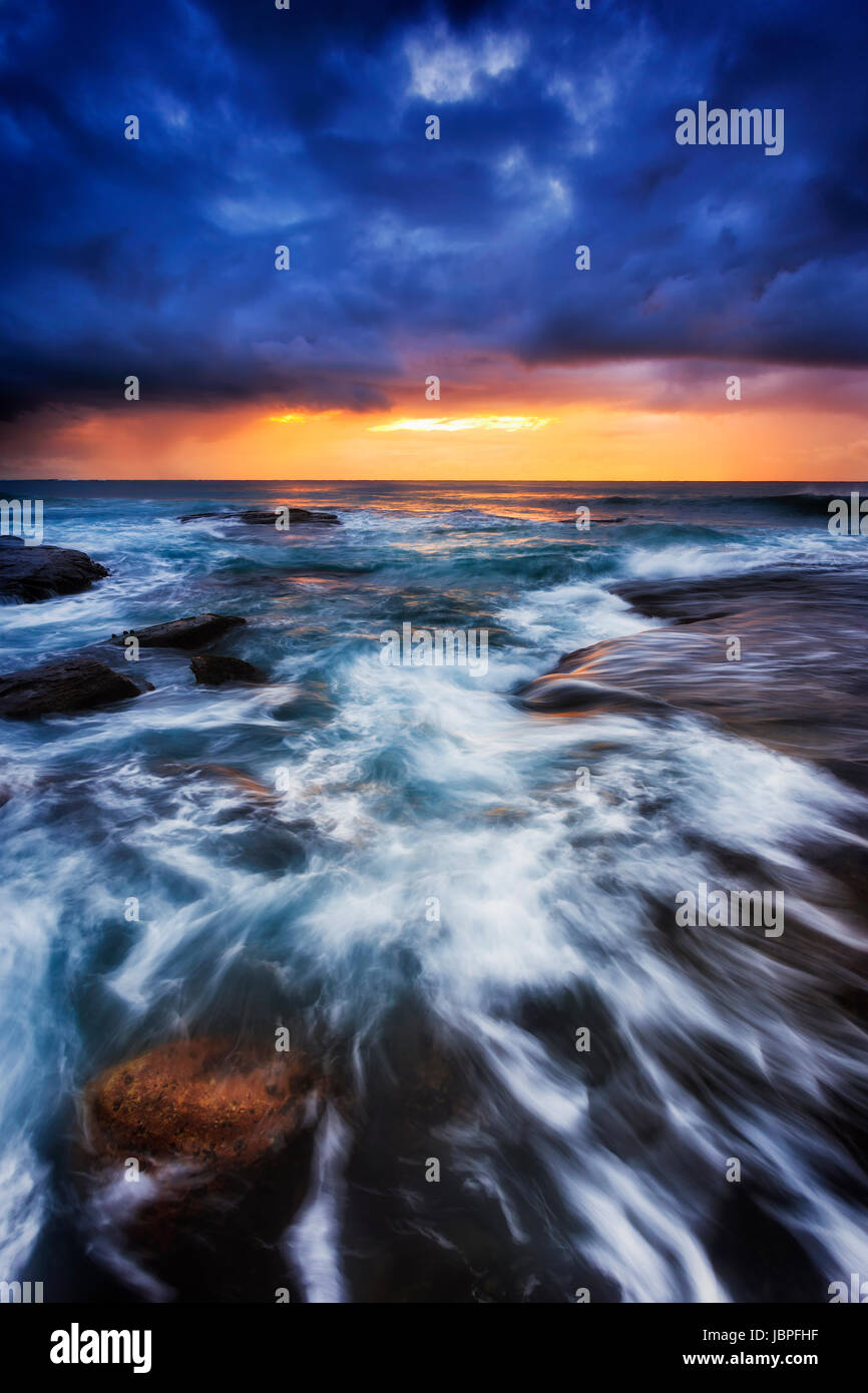 Dark dawn time at Bungan beach of Pacific coast in Sydney, Australia. Strong waves roll on eroded boulders under - Stock Image