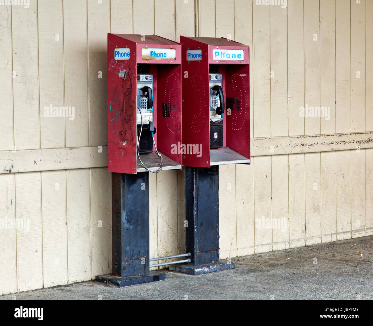 Abandoned coin operated public pay telephones with coin release slot. - Stock Image