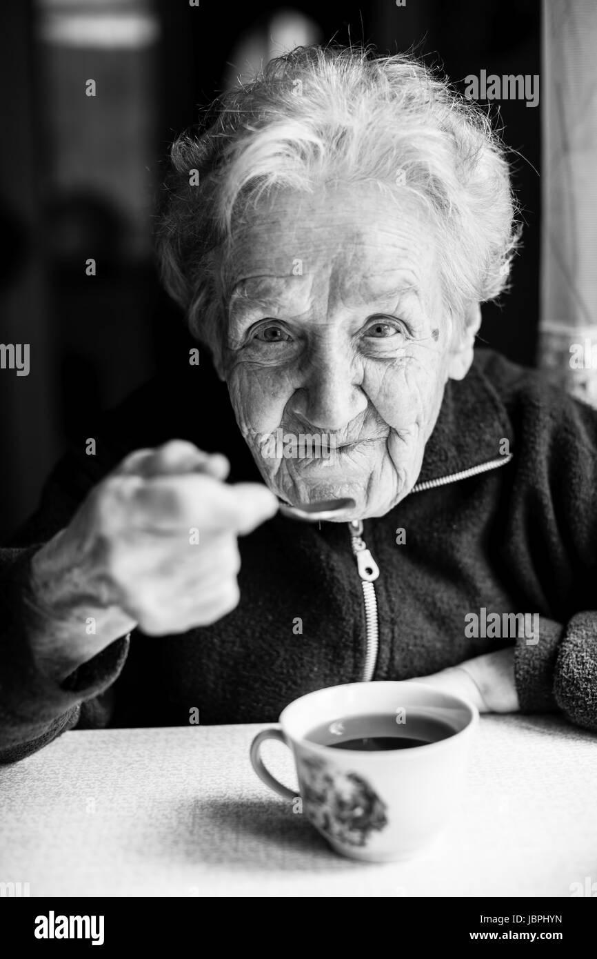 Stock photo enlarge elderly woman drinking tea closeup black and white portrait of russian grandmother