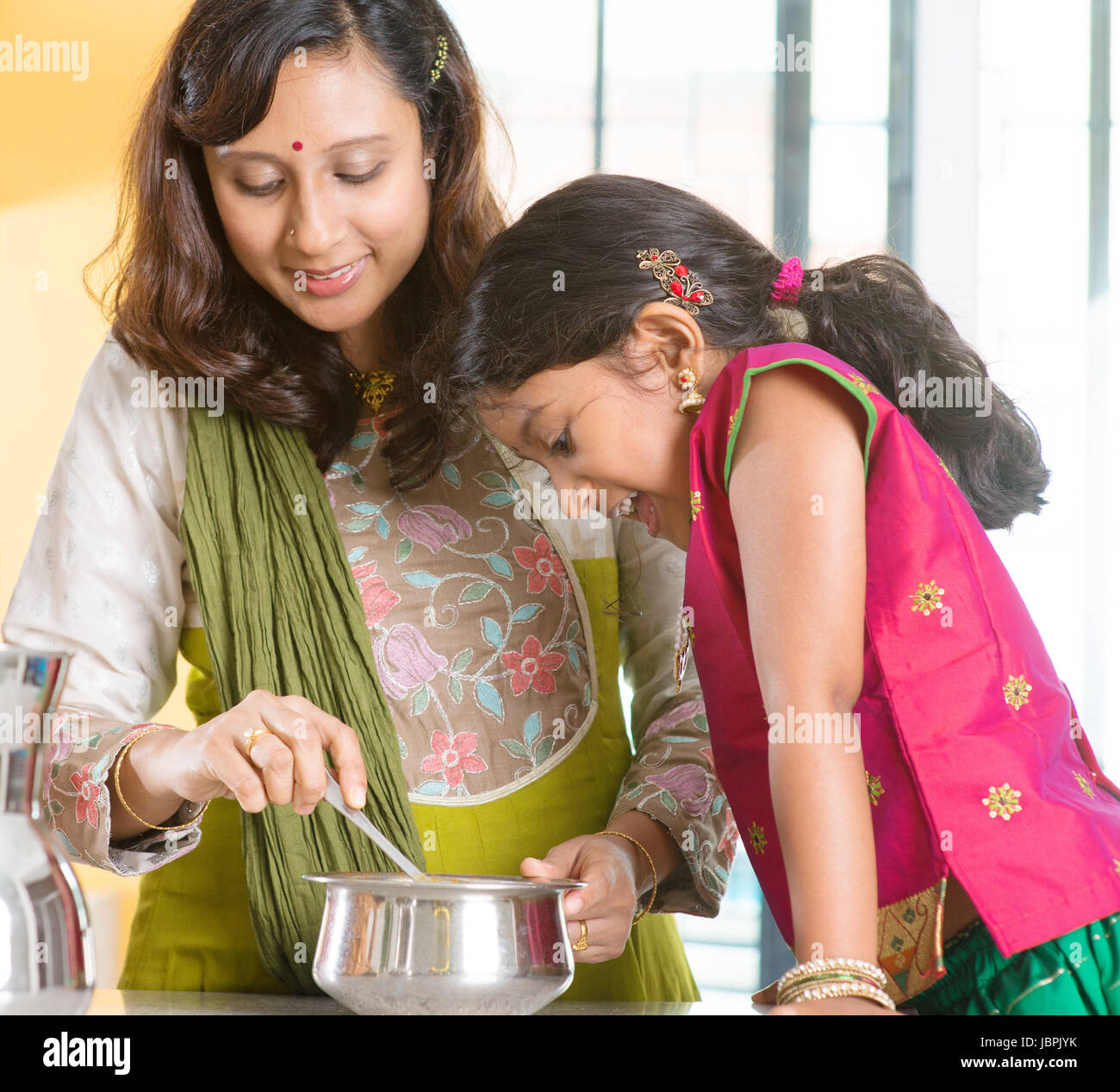 Asian family cooking food together at home indian mother and child asian family cooking food together at home indian mother and child preparing meal in kitchen traditional india people with sari clothing forumfinder Images