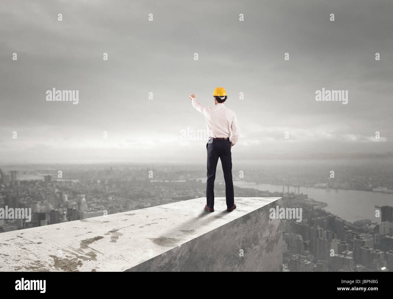 Businessman with helmet indicates the right direction - Stock Image