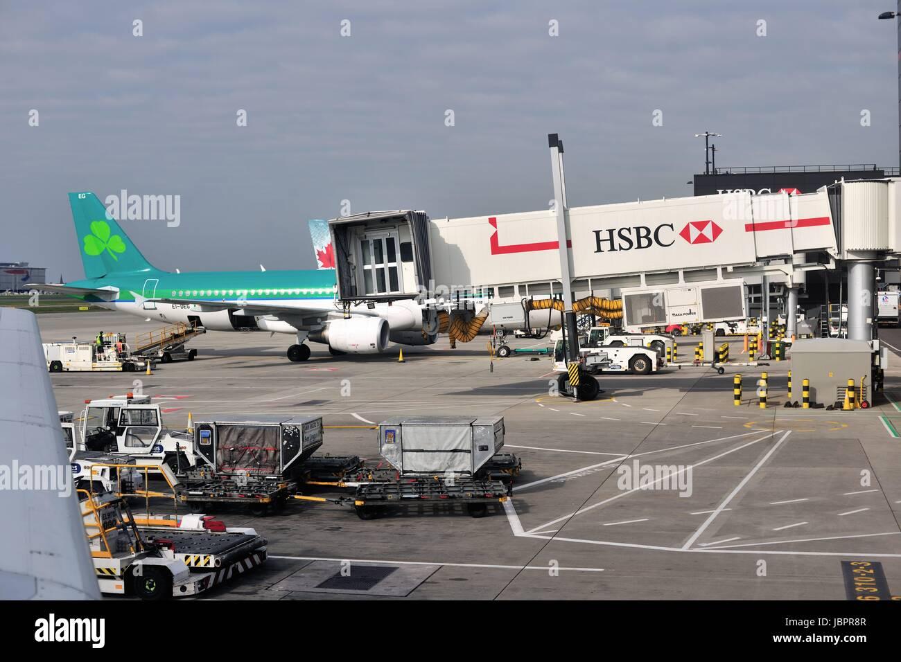 Aer Lingus aircraft at terminal building amidst activity at London's Heathrow International Airport. London, - Stock Image