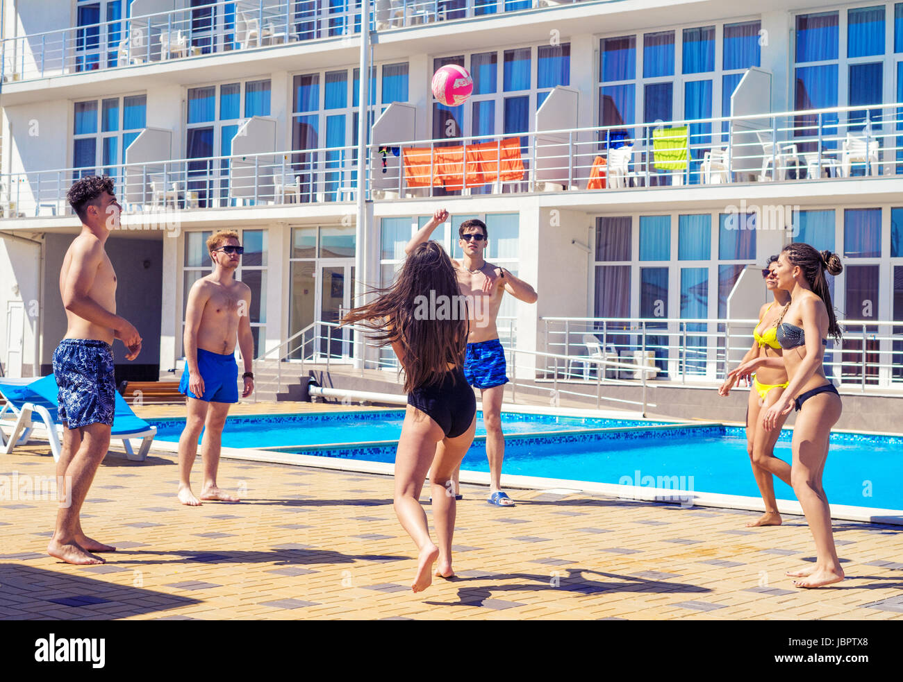 Group of cheerful couples friends playing volleyball - Stock Image
