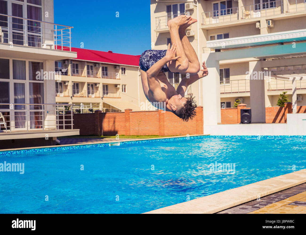 Man doing Somersaul or flip diving into swimming pool - Stock Image