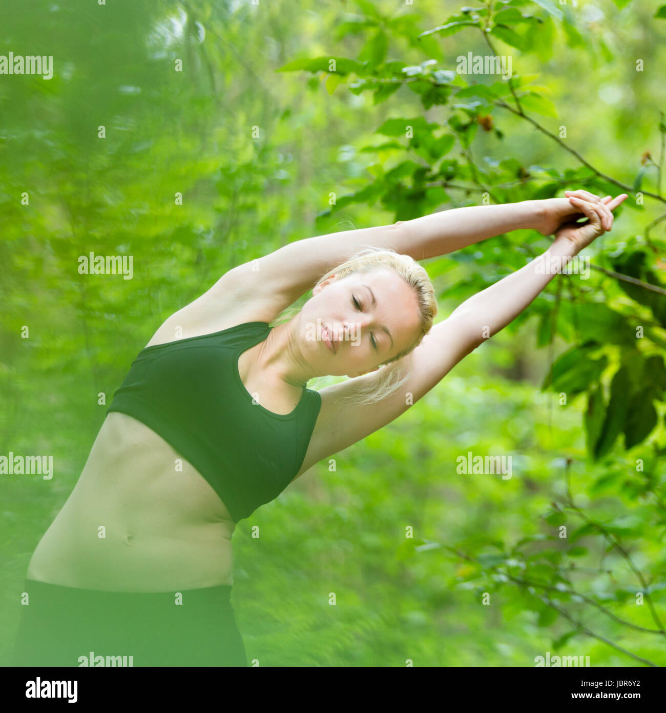 Young caucasian lady is practicing half moon yoga pose in the nature. - Stock Image