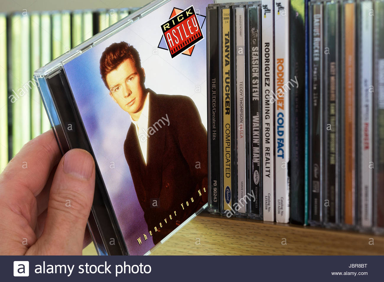 Whenever You Need Somebody, 1987 Rick Astley CD being chosen from a shelf of other CD's, Dorset, England - Stock Image