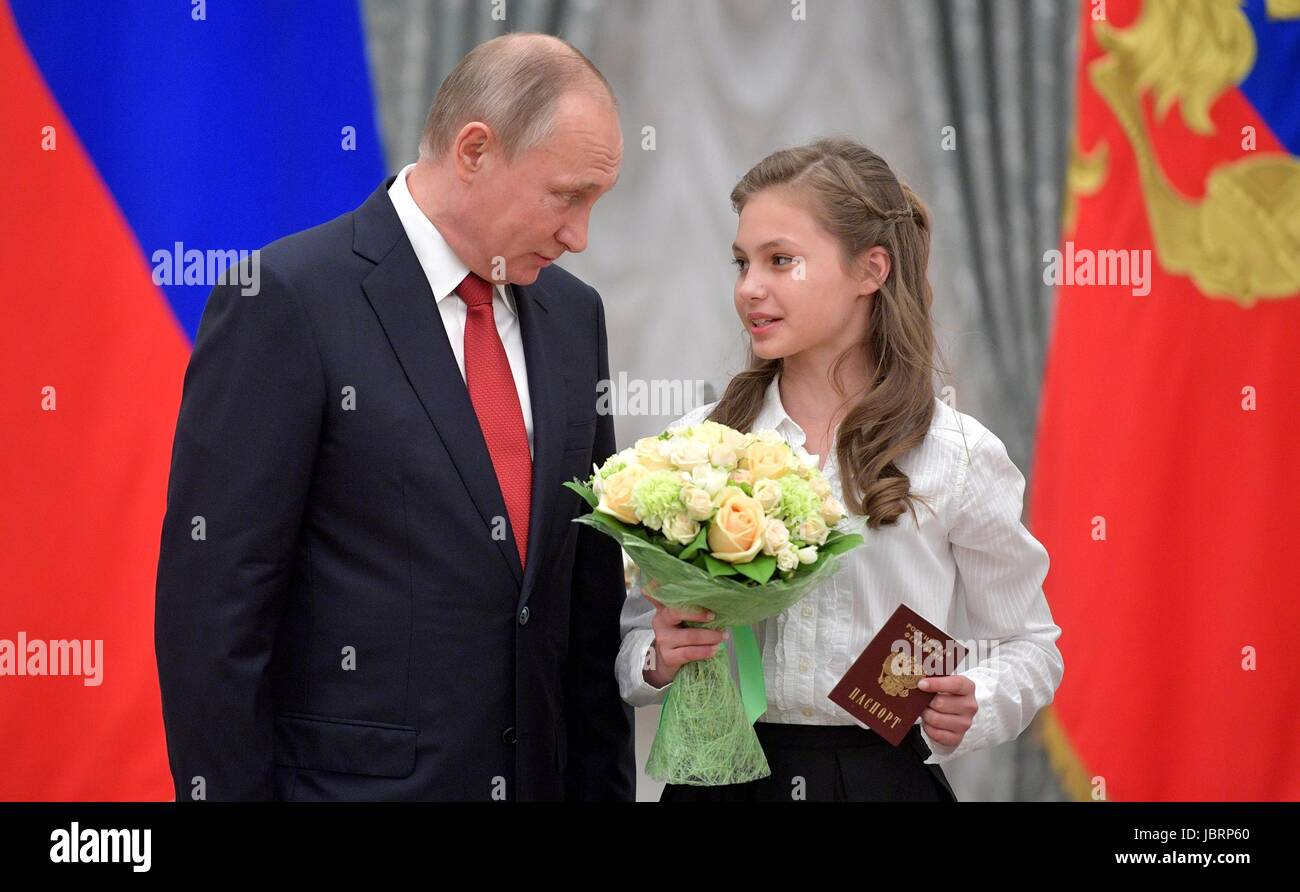Russian President Vladimir Putin speaks to a young girl after presenting her with a Russian passport during a ceremony Stock Photo