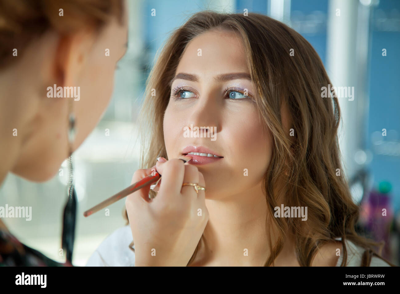 Make up artist doing professional makeup of young woman - Stock Image
